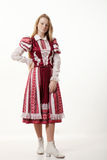 Young beautiful redhead folk dancer woman with gorgeous long hair in traditional authentic folk costume posing isolated on white. Young beautiful redhead folk stock image