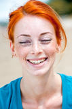 Young beautiful redhead freckled woman smiling. Outdoor portrait of a young beautiful redhead freckled woman smiling happily with her eyes closed Royalty Free Stock Photography