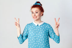 Young beautiful redhead girl with blue dress and head band showing peace sign. Isolated studio shot on gray background royalty free stock photo