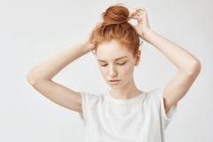 Young beautiful redhead girl correcting hair bun. Stock Images