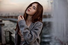 Young beautiful redhead girl posing in gray coat and beige blouse near artificial water channel.  royalty free stock images