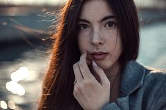 Young beautiful redhead girl posing in gray coat and beige blouse near artificial water channel royalty free stock photography