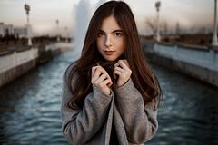 Young beautiful redhead girl posing in gray coat and beige blouse near artificial water channel.  stock photo