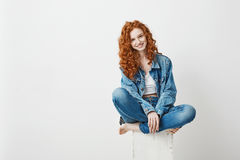 Young beautiful redhead girl smiling looking at camera sitting on box over white background. Copy space. stock photos