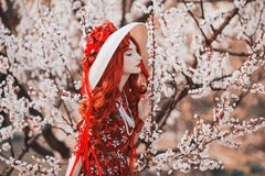 Young beautiful redhead girl on spring flower garden. Woman with long red hair in dress sniff flower on nature. Sweet aroma.