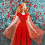 Young beautiful redhead girl with very long hair braided in plait with rose on her head. Fabulous renaissance woman in a red dress against the backdrop of a royalty free stock images