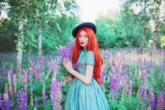 Young beautiful redhead girl with very long hair on lupine background. Fabulous renaissance woman in mint dress against the backdr. Op of a beautiful flowers royalty free stock photography