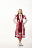 Young beautiful redhead lady dancer in traditional folk costume posing isolated on white background Stock Image