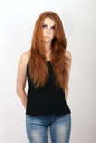 Young beautiful redhead model in black t-shirt  and blue jeans with violet eyes makeup posing against gray studio background Stock Photo