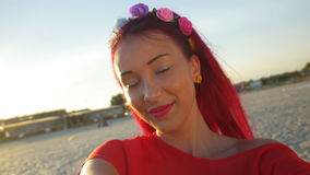 Young beautiful redhead posing on the beach and taking a selfie stock video footage
