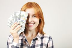 Attractive young businesswoman posing with bunch of USD cash in hands showing positive emotions and happy facial expression. royalty free stock photos
