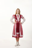 Young beautiful redhead woman dancer in traditional folk costume posing isolated on white background Royalty Free Stock Photography
