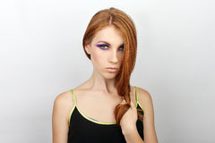 Young beautiful redhead woman with gorgeous hair and violet eyes makeup in black t-shirt against white studio background Stock Photos