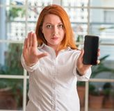 Young beautiful redhead woman at home. Redhead woman using smartphone at home with open hand doing stop sign with serious and confident expression, defense royalty free stock photo