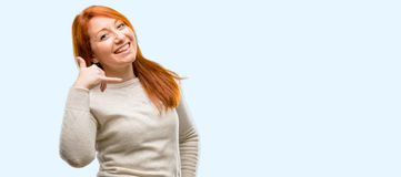 Young beautiful redhead woman over blue background royalty free stock photos