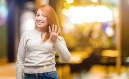 Young beautiful redhead woman over night background. Beautiful young redhead woman raising finger, is the number four at night royalty free stock photography