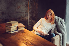 Young beautiful redhead woman relaxing at home in the autumn cozy evening and reading book Stock Photos
