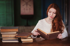 Young beautiful redhead woman relaxing at home in the autumn cozy evening and reading book Royalty Free Stock Image