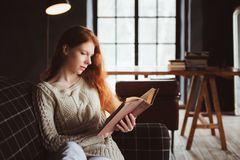 Young beautiful redhead woman relaxing at home in the autumn cozy evening and reading book Royalty Free Stock Images