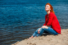 Young beautiful redhead woman sitting at the beach. Redhead woman sitting comfortably and smiling, looks serene and free and enjoying a sunny day at the beach Stock Photos