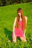 Young beautiful redhead woman sitting on grass Stock Photo