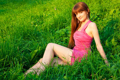 Young beautiful redhead woman sitting on grass Royalty Free Stock Image
