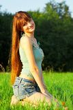 Young beautiful redhead woman sitting on grass Stock Photography