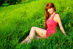 Young beautiful redhead woman sitting on grass Royalty Free Stock Photography