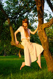 Young beautiful redhead woman sitting on tree Royalty Free Stock Images