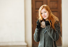 Young beautiful redhead woman wearing coat and scarf posing outdoors with architectural background Royalty Free Stock Photos