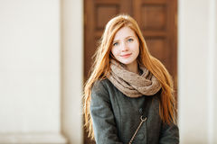Young beautiful redhead woman wearing coat and scarf posing outdoors with architectural background Royalty Free Stock Photography