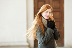 Young beautiful redhead woman wearing coat and scarf posing outdoors with architectural background royalty free stock images