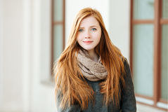 Young beautiful redhead woman wearing coat and scarf posing outdoors with architectural background Stock Photos