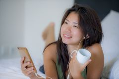 Young beautiful Asian Chinese woman with earpiece listening to music smiling happy lying on bed using internet on mobile phone Stock Photography