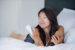 Young beautiful Asian Chinese woman with earpiece listening to music smiling happy lying on bed using internet on mobile phone Royalty Free Stock Photos