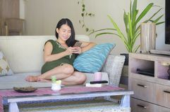 Young beautiful and relaxed Asian Chinese woman lying at home living room sofa couch using internet on mobile phone happy and comf Stock Images
