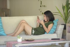 Young beautiful and relaxed Asian Chinese woman lying at home living room sofa couch using internet on mobile phone happy and comf Royalty Free Stock Photography