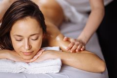 Relaxing woman getting spa massage of shoulder in beauty salon Stock Image