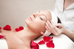 Young beautiful relaxing woman having a facial massage Stock Images