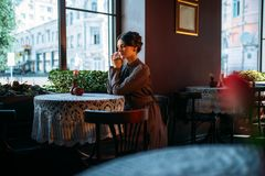 Young beautiful retro lady in cafe. Sitting near window. Beautiful young girl resting in a cafe and smiling. Dark hair woman looking in window in vintage style Royalty Free Stock Photography