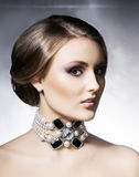 Young, beautiful and rich woman in jewels. Metal background royalty free stock image