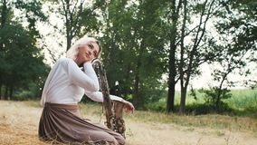 Young beautiful romantic girl sitting on the ground on hay on the ground with a saxophone, a woman with a musical instrument, conc. Ept hobby, music, lifestyle stock footage