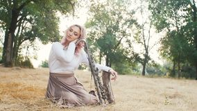 Young beautiful romantic girl sitting on the ground on hay on the ground with a saxophone, a woman with a musical instrument, conc. Ept hobby, music, lifestyle stock video footage