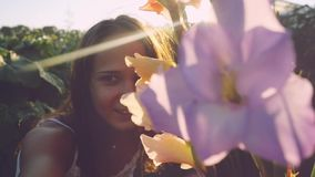 Young beautiful romantic woman in flowers outdoor at sunset through the sun in slow motion with lense flare effects. Young beautiful woman in flowers outdoor at stock video