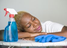 Young beautiful sad and depressed afro American black woman tired and exhausted sleeping at home kitchen overworked cleaning and w Royalty Free Stock Photos
