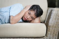 Young beautiful sad and depressed Asian Chinese woman at home sofa couch feeling overwhelmed suffering anxiety crisis and stock photography