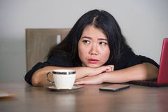 Asian Korean businesswoman working in stress at office computer desk feeling overwhelmed and frustrated suffering depression think stock image