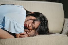 Young beautiful sad and depressed Asian Korean woman at home sofa couch feeling overwhelmed suffering anxiety crisis and stock photo