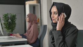 Young beautiful sad girl in black hijab sits in the office and speaks on the smartphone. Unhappy 60 fps. 4k stock video footage
