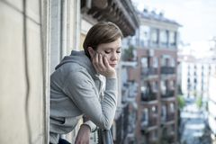 Young beautiful sad and unhappy woman suffering from depression looking thoughtful on the balcony. Young attractive, unhappy sad caucasian woman suffering from royalty free stock photo